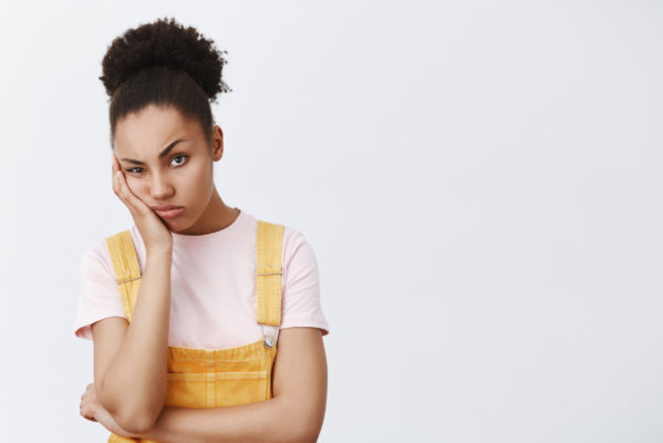 Woman hates when friend complaining on her life, staring with indifferent and bored expression, leaning on palm, frowning and pouting, being tired and annoyed over gray background